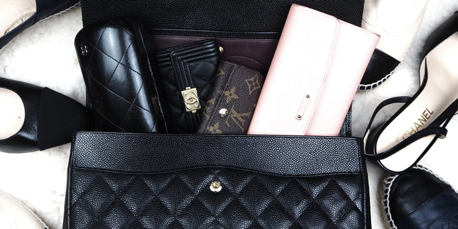 196f6a60fdb8 An opened black caviar classic flap bag from Chanel showing small leather  goods and surrounded by